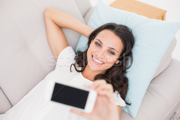 Stock photo: Pretty brunette taking a selfie on couch