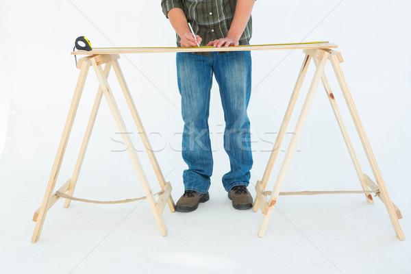 Construction worker marking wooden table Stock photo © wavebreak_media
