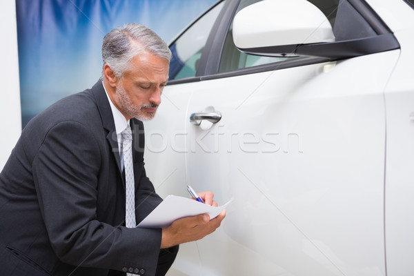 Businessman looking at car while writing on clipboard Stock photo © wavebreak_media
