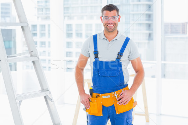 Smiling repairman in overalls at bright office Stock photo © wavebreak_media