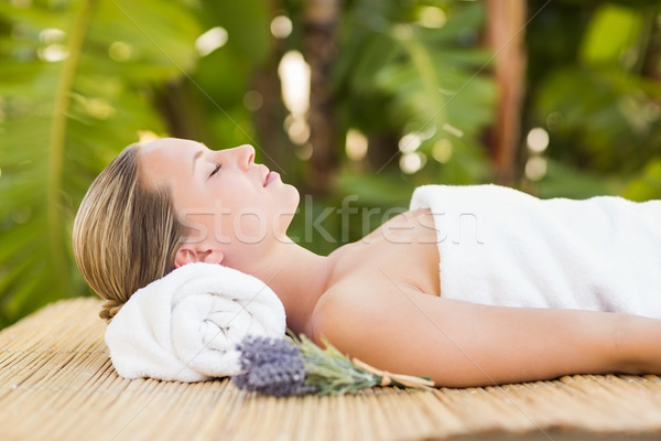 Peaceful blonde lying on bamboo mat with flowers Stock photo © wavebreak_media