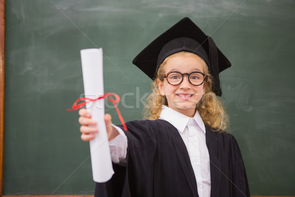 Pupil with graduation robe and holding her diploma Stock photo © wavebreak_media