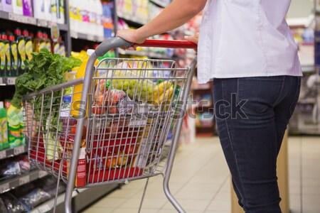 Bastante morena empurrando olhando prateleira supermercado Foto stock © wavebreak_media