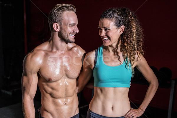 Muskularny para patrząc inny uśmiechnięty kobieta Zdjęcia stock © wavebreak_media