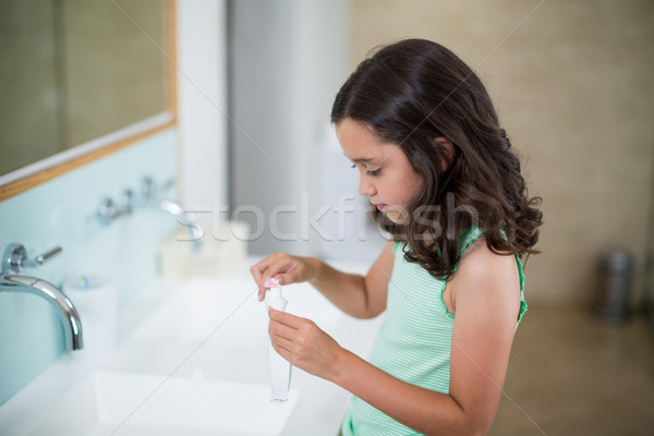 Girl putting toothpaste on brush in bathroom Stock photo © wavebreak_media