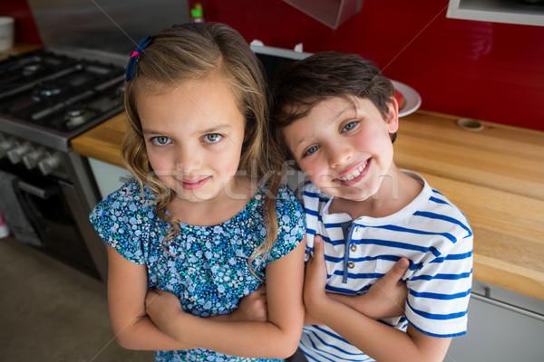 Happy siblings standing with arms crossed in kitchen Stock photo © wavebreak_media