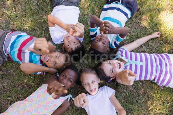 Portrait of smiling friends pointing up while lying on grassy field Stock photo © wavebreak_media