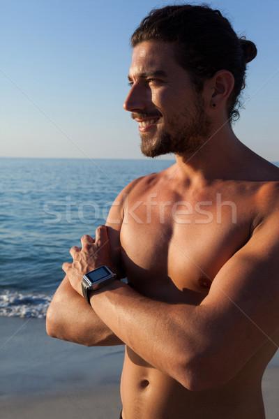 Muscular hombre pie los brazos cruzados playa sonriendo Foto stock © wavebreak_media