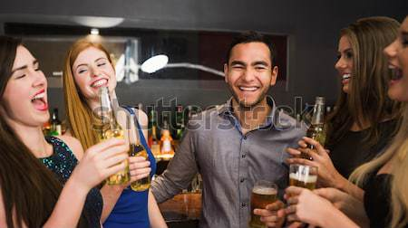 Portrait of smiling woman holding wineglass with friends at nightclub Stock photo © wavebreak_media