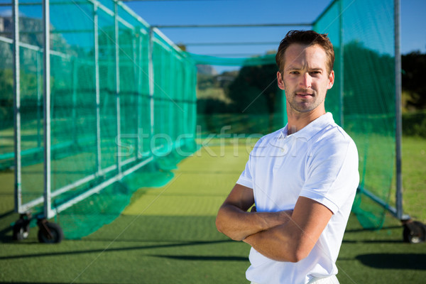Portrait of young cricketer with arms crossed standing on field Stock photo © wavebreak_media