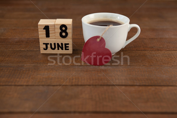 Calender date by coffee cup with heart shape on wooden table Stock photo © wavebreak_media