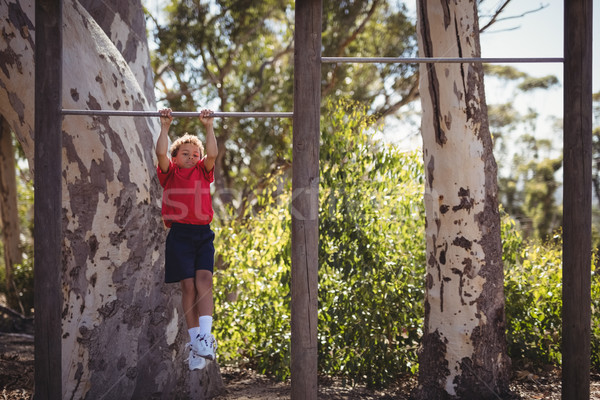 Boy performing pull-ups on bar during obstacle course Stock photo © wavebreak_media