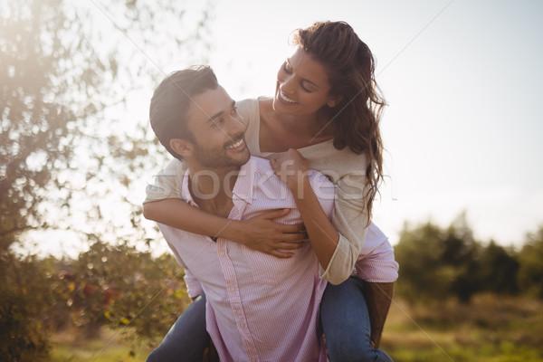 Young man piggybacking woman at farm during sunny day Stock photo © wavebreak_media