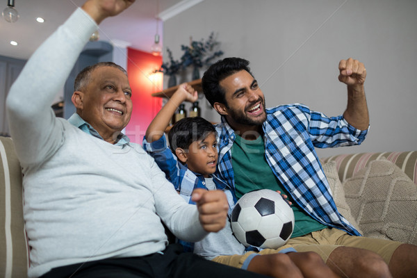 Happy family with arms raised watching soccer match Stock photo © wavebreak_media