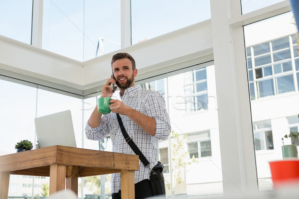 Businessman having drink while talking on phone while standing at desk Stock photo © wavebreak_media