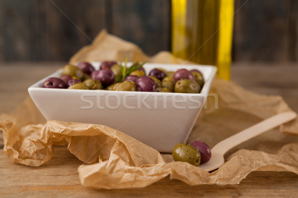 Close up of olives served in bowl by wooden spoon Stock photo © wavebreak_media