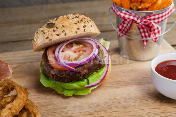 Hamburger, french fries, onion ring and tomato sauce on chopping board Stock photo © wavebreak_media