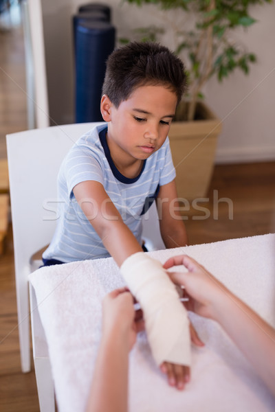 Boy looking at female therapist wrapping bandage on hand Stock photo © wavebreak_media
