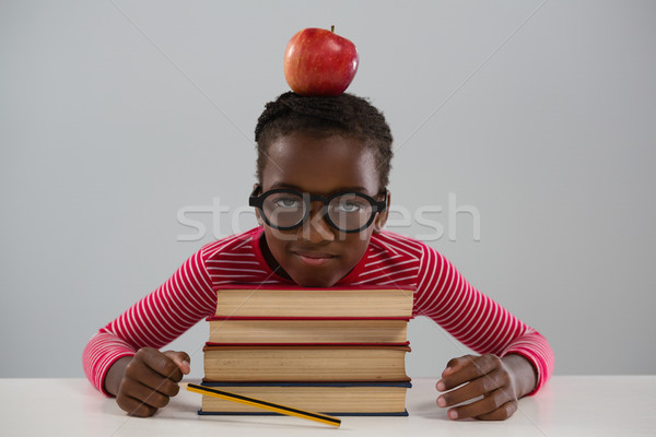 Schoolgirl leaning on books stack against white background Stock photo © wavebreak_media
