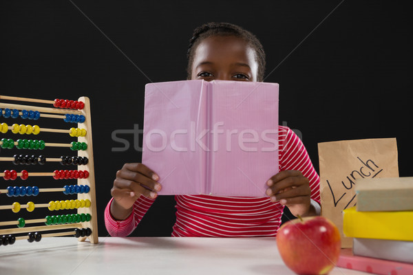 Schoolgirl hiding face behind book against black background Stock photo © wavebreak_media
