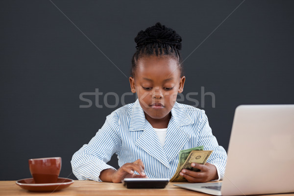 Serious businesswoman calculating paper currency Stock photo © wavebreak_media