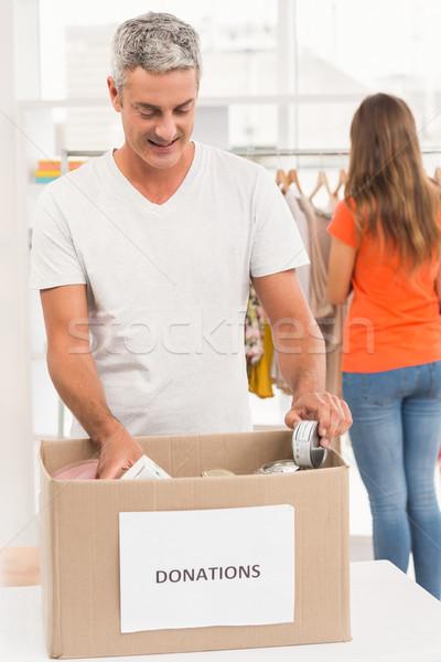 Smiling casual businessman sorting donations Stock photo © wavebreak_media