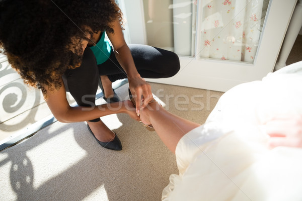 High angle view of beautician putting on sandal to bride Stock photo © wavebreak_media