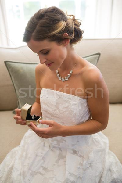 Hermosa novia mirando anillo de bodas sesión sofá Foto stock © wavebreak_media