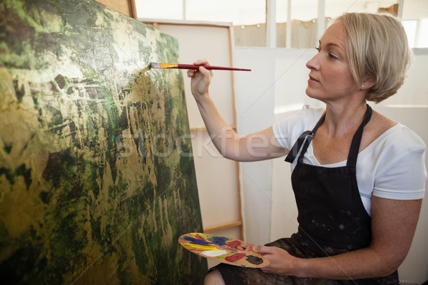 Attentive woman painting on canvas Stock photo © wavebreak_media