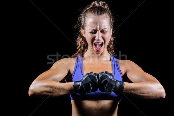 Aggressive female boxer flexing muscles Stock photo © wavebreak_media