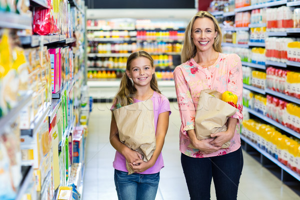 Smiling mother and daughter with grocery bags Stock photo © wavebreak_media
