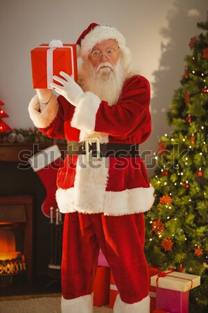 Santa claus with finger on lips in living room during christmas time Stock photo © wavebreak_media