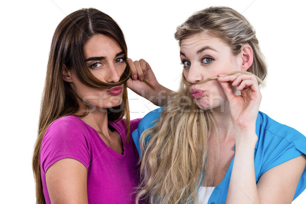 Portrait of mischievous friends playing with hair  Stock photo © wavebreak_media