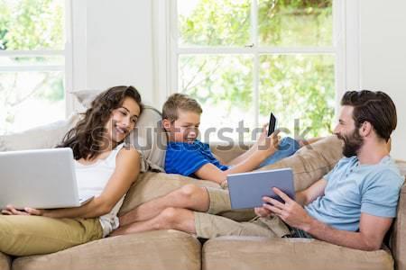 молодые друзей глядя ноутбука сидят диван Сток-фото © wavebreak_media