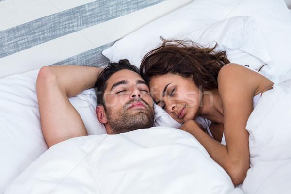 Couple with eyes closed while sleeping on bed Stock photo © wavebreak_media