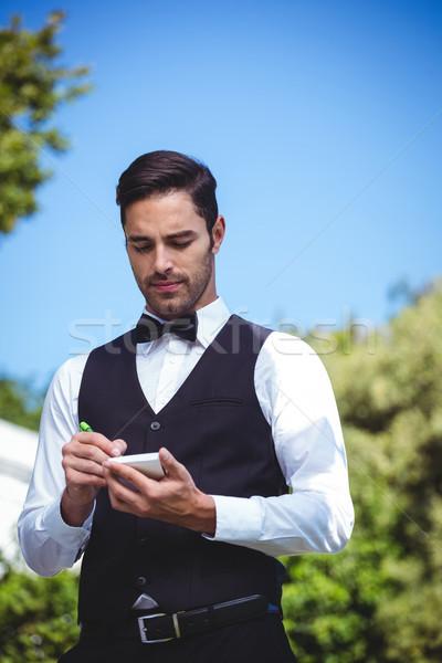 élégant garçon écrit ordre à l'extérieur restaurant Photo stock © wavebreak_media