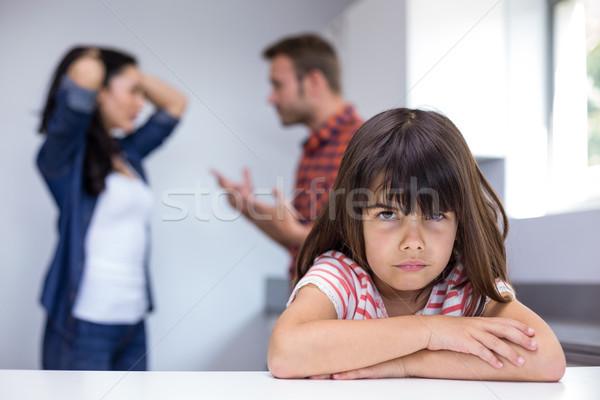 Stock photo: Sad girl hearing her parents arguing
