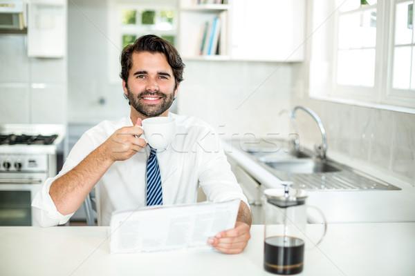 Confident businessman drinking coffee while reading newspaper Stock photo © wavebreak_media