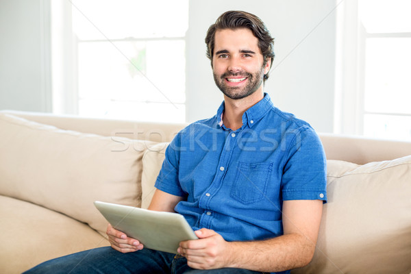 Przystojny mężczyzna cyfrowe tabletka posiedzenia sofa portret Zdjęcia stock © wavebreak_media