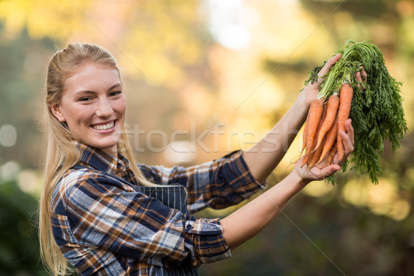 Young female gardener holding harvested carrots Stock photo © wavebreak_media
