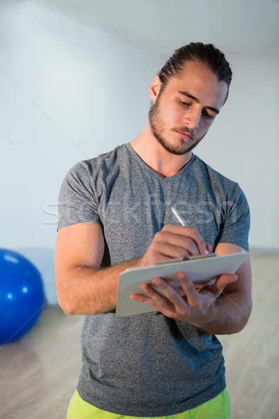 Fitness trainer writing on clipboard Stock photo © wavebreak_media