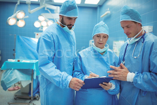 Male and female surgeon discussing over clipboard in operation theater Stock photo © wavebreak_media
