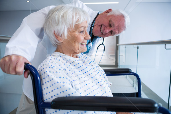 Doctor holding senior patient on wheelchair in passageway Stock photo © wavebreak_media