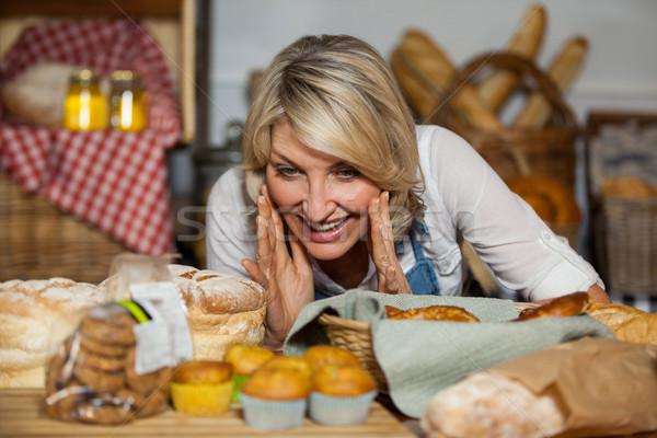 Female staff looking at various sweet food Stock photo © wavebreak_media