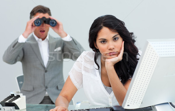 Brunette businesswoman annoyed by a man looking through binocula Stock photo © wavebreak_media