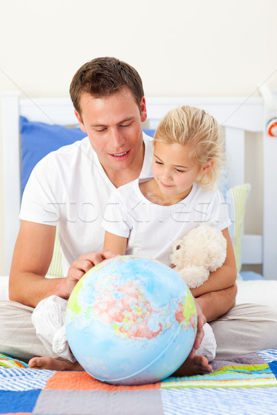 Attentive father and his daughter looking at a terretrial globe Stock photo © wavebreak_media