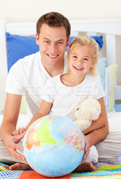 Attentive father and his daugther looking at a terrestrial globe Stock photo © wavebreak_media