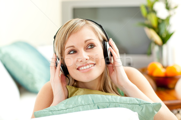 Encantador rubio mujer escuchar música sofá Foto stock © wavebreak_media