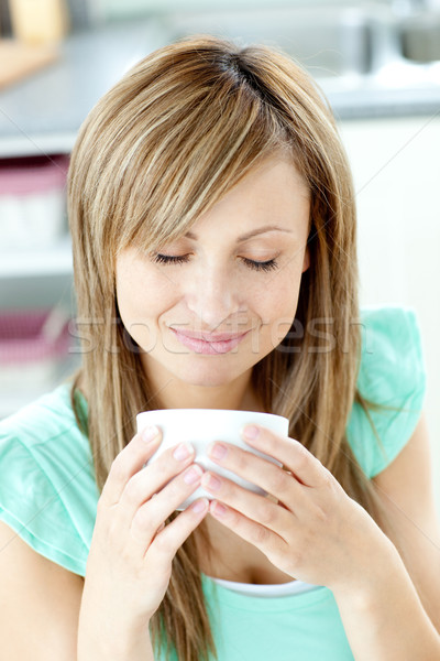 Delighted woman holding a cup of coffee in the kitchen  Stock photo © wavebreak_media