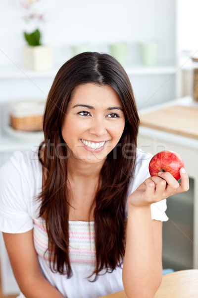 Radiant asian woman holding an apple in the kitchen at home Stock photo © wavebreak_media
